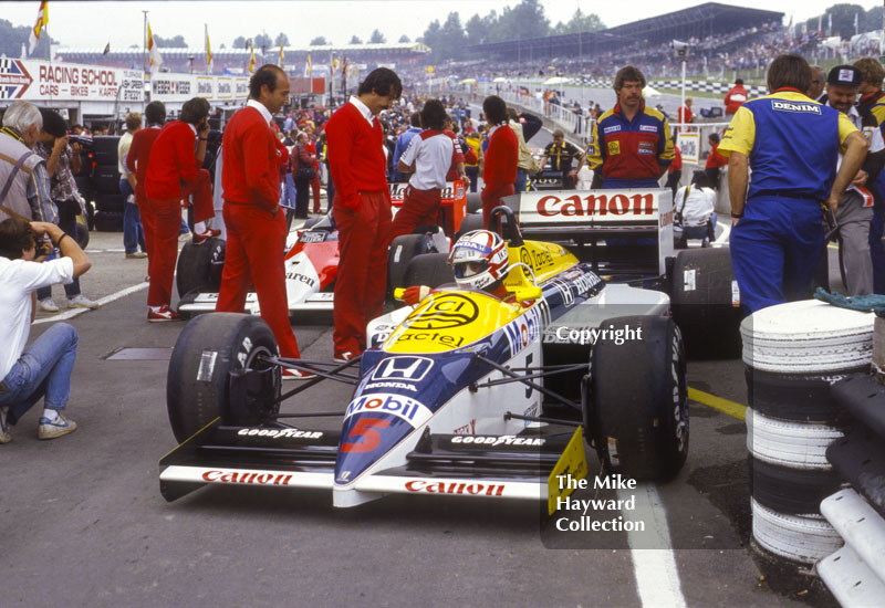 Nigel Mansell, Williams Honda FW11, surrounded by McLaren pit crew, Brands Hatch, 1986 British Grand Prix.