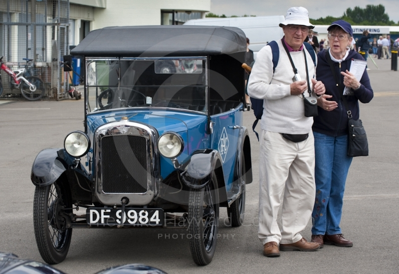 Elderly couple next to an RAC Austin Seven car in the paddock, Silverstone Classic 2010