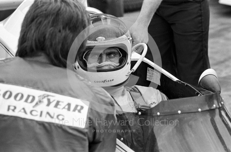 Carlos Reutemann, Brabham, chats to a mechanic on the grid before the start of the 1974 British Grand Prix at Brands Hatch.