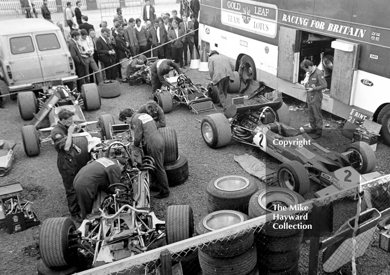 Gold Leaf Team Lotus mechanics working on the 49B's of Graham Hill and Jochen Rindt in the paddock, Silverstone, British Grand Prix 1969.