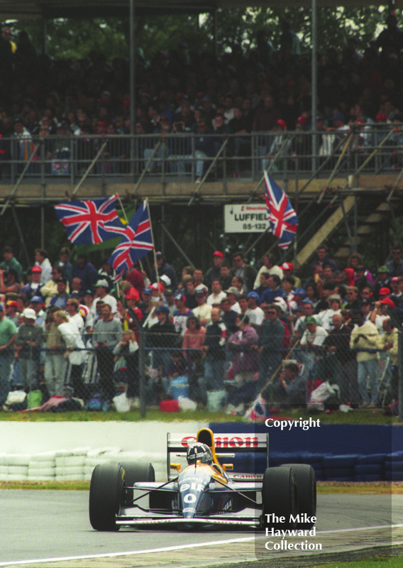 Damon Hill, Williams Renault FW15C, in front of packed grandstands at Woodcote during the 1993 British Grand Prix at Silverstone.