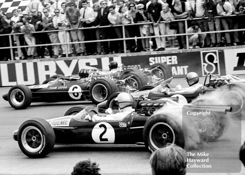Jim Clark and Graham Hill, Lotus Cosworth 49s, and Jack Brabham and Denny Hulme, Repco Brabham BT24 V8s, leave the grid at Silverstone, 1967 British Grand Prix.