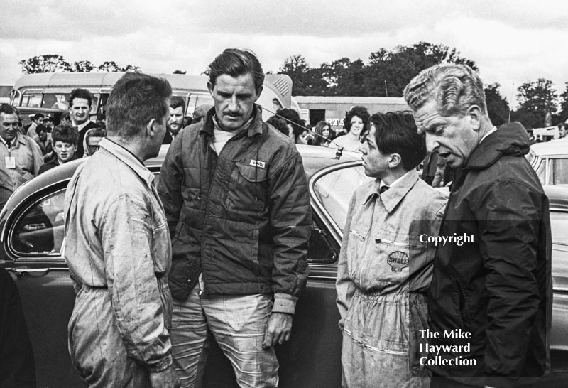 Graham Hill and John Coombes talk to mechanics in the paddock, Oulton Park Gold Cup meeting, 1964.