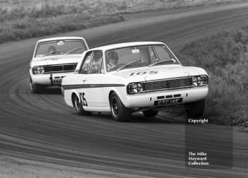 Team mates Graham Hill, CTC 14E, and Jacky Ickx, CTC 24E, driving Team Lotus Ford Cortinas at the Oulton Park Gold Cup meeting in 1967. Hill - who is on three wheels - and Ickx are pictured at Cascades Bend.