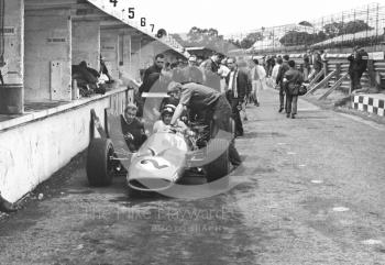 The McLaren Ford M7A of Bruce McLaren receives attention during practice for the 1968 British Grand Prix at Brands Hatch.