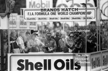 Nigel Mansell, Ayrton Senna Keke Rosberg celebrate on the podium, Brands Hatch, 1985 European Grand Prix. Alain Prost is also on the podium as he won the championship by finishing fourth at this race.