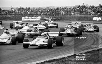 First lap of heat two at copse corner, Silverstone, 1971 International Trophy. Brian Redman, McLaren M18, with Jean-Pierre Beltoise, Matra MS120B, Henri Pescarolo, March 711 and Tim Schenken, Brabham BT33.