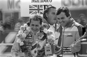 Roberto Moreno and Alan Jones on the podium with commentator Peter Scott-Russell, Marlboro British Formula 3 championship held at the 1981 Grand Prix, Silverstone.