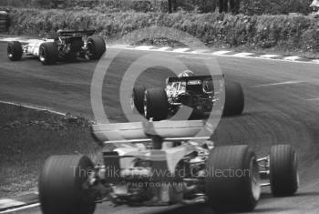 Denny Hulme, Mclaren M14D, and Clay Regazzoni, Ferrari 312B, follow a BRM through Stirling's Bend, British Grand Prix, Brands Hatch, 1970