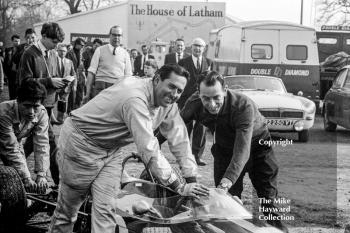 Driver Jack Brabham and designer Ron Tauranac push the Brabham Honda through the paddock at the Oulton Park Spring International meeting in 1965. The car was making its debut and Brabham offered to withdraw it from the race due to lack of speed (14mph slower on the straight than Graham Hill's Brabham BRM) but eventually it did start, lasting until lap 17.