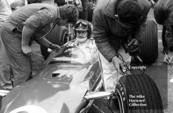 A technician checks the Firestone tyres on Graham Hill's Gold Leaf Team Lotus 49 during practice for the 1968 British Grand Prix at Brands Hatch.