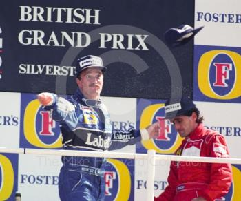 Nigel Mansell, Williams FW14, throws his cap to the crowd after winning the 1991 British Grand Prix at Silverstone.