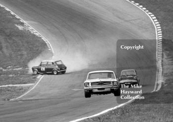 B Thomson, Ford Mustang, and Anita Taylor, Broadspeed Ford Anglia, take the right line as Bill Shaw, Mini Cooper S, investigates the infield at Paddock Bend, British Touring Car Championship Race, Guards International meeting, Brands Hatch 1967.