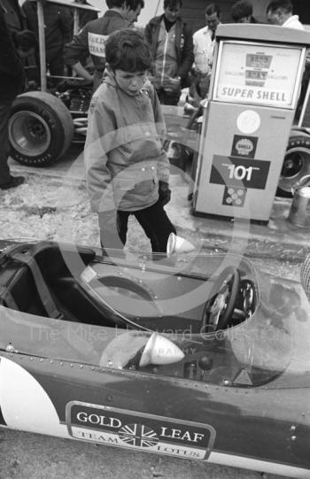A young admirer studies the cockpit of Graham Hill's Gold Leaf Team Lotus 49B as mechanics fill up the cars at the paddock pumps, Silverstone, International Trophy 1969.